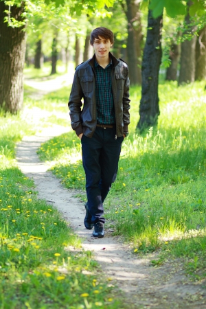 Young man walks on path in city park photo