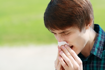 transmitted: Young man sneezing outdoor and blowing his nose because he has allergies.  Stock Photo