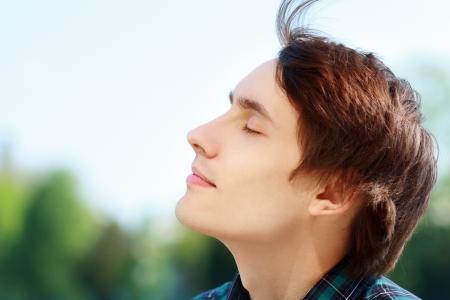 aire puro: Joven atractivo hombre de respiración de aire fresco al aire libre que muestra su cara al viento