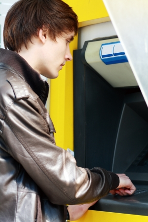 withdrawing: young man student withdrawing money from an atm cash machine