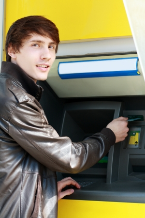 withdrawing: young man student withdrawing money from a  bank cash point, outdoors