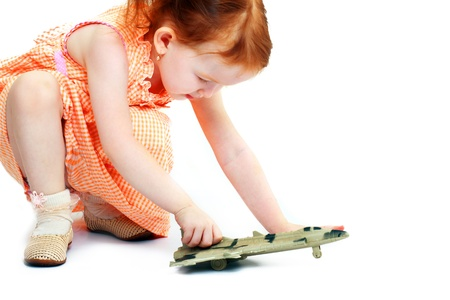 Cute little girl playing with a toy airplane. Isolated on white background  photo