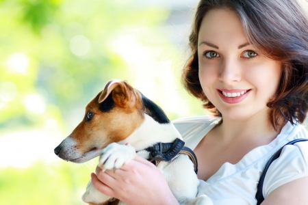 woman beautiful young happy with dark hair in striped sweater holding small dog Jack Russell Terrier photo