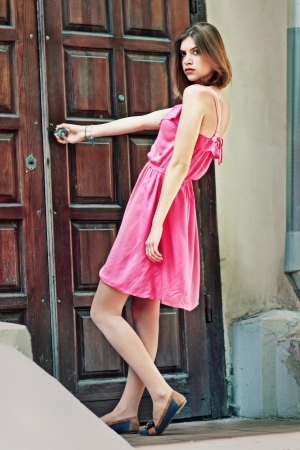 beautiful woman trying to open the old door in the city photo