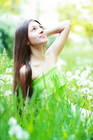 Spring Beauty Girl. Beautiful Young Woman Lying on Green Grass outdoor. Park. Meadow. Summer. Spring Girl on the Field. Happiness. Outdoors. Youth concept  photo
