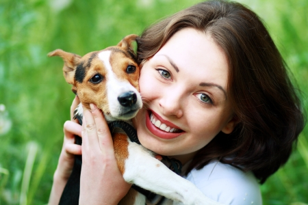 woman beautiful young happy with dark hair in striped sweater holding small dog Jack Russell Terrier