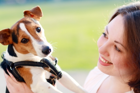 woman beautiful young happy with dark hair holding small dog Jack Russell Terrier photo