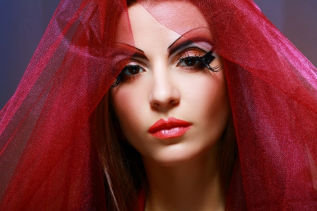 Young woman with creative visage in red shawl photo