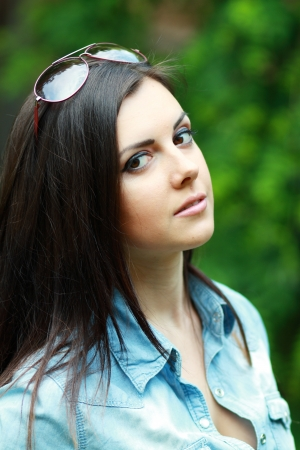 Portrait close up of young beautiful woman outdoor in green park photo
