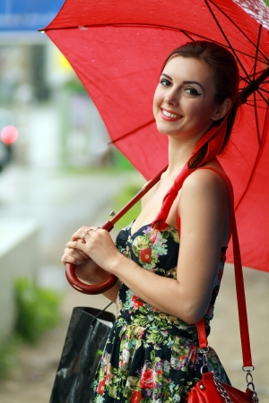 Beautiful brunette woman holding red umbrella out in the rain photo