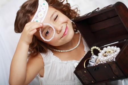 schöne kleine Mädchen spielt mit Mutter Schmuck hautnah