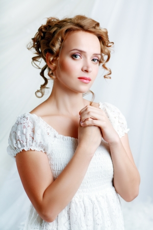 Beautiful woman with romantic bride hairstyle wearing in white wedding dress posing in interior apartment photo