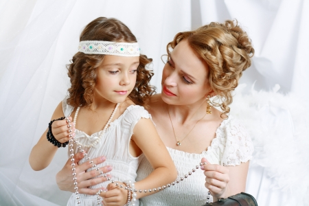 Smiling mother and baby daughter playing with jewelry photo