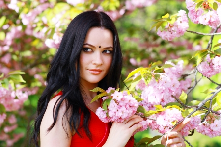 beautiful asian indian woman in the park on a warm spring day with blossom flowers around her photo