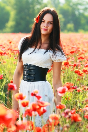 sexy angel: beauty woman in poppy field in white dress in a sunny summer day