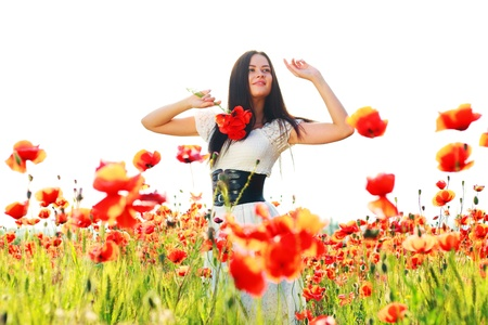 sexy angel: beauty woman in poppy field in white dress in a sunny summer day