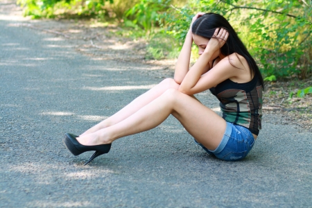 Sad girl sitting down on road hiding her head on her hands photo