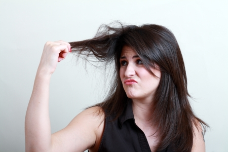 Charming brunette is not happy with fragile hair photo