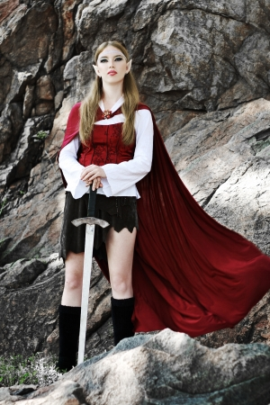 Elf girl on the rock in red cloak posing outdoor photo