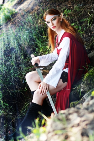 elfin: Elf girl on the rock in red cloak posing outdoor