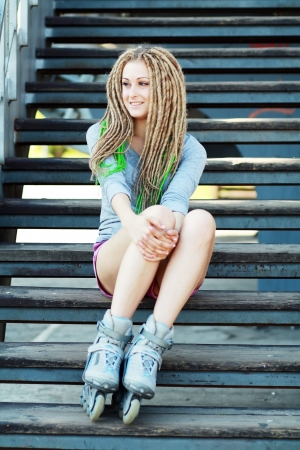 portrait of a beautiful girl with dreadlocks with rollerskates on her legs photo