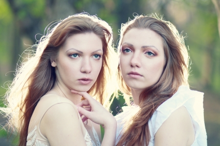two Beautiful woman twins in the morning park focus on one of the sisters photo