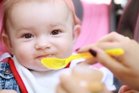 smeared baby: Coma manchado muchacha bonita del beb� que come de la cuchara al aire libre Foto de archivo