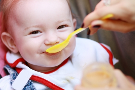 eat smeared baby: Eat smeared pretty baby girl eating from spoon outdoor