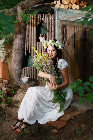 a fairy girl sitting near the forest house of dwarfs   photo