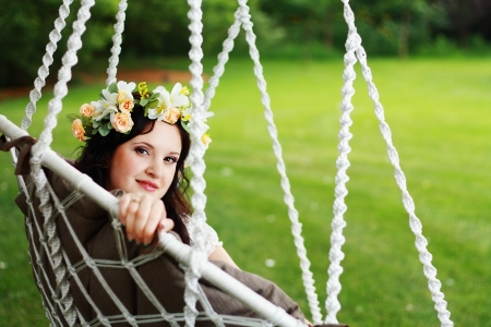 young beautiful woman swinging on natural background photo