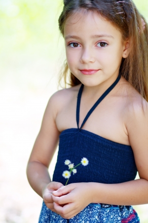 beautiful little girl on the meadow in summer day photo