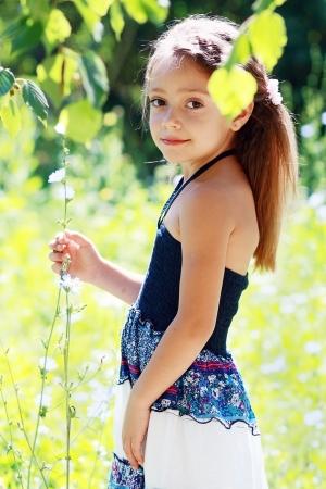 florecitas: hermosa niña de seis años en el prado en día de verano