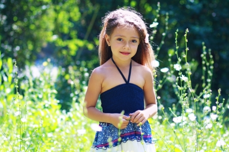 beautiful little girl on the meadow in summer day face close up