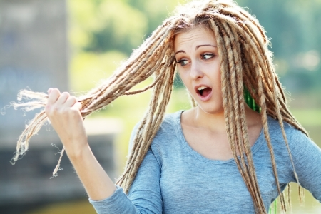 Charming woman wiith dreadlocks is not happy with fragile hair photo