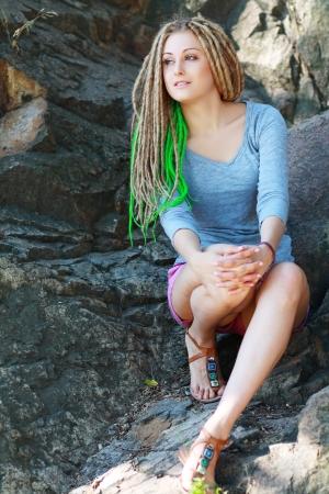 dreadlocks: Chica inconformista joven con trenzas posando al aire libre sentado en la roca Foto de archivo
