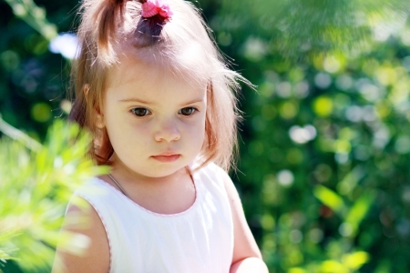 expresses: Adorable little girl serene and still. Her face expresses a thoughtful and contemplative look as she enjoys the outdoors. 1,5 years or 2 years Stock Photo