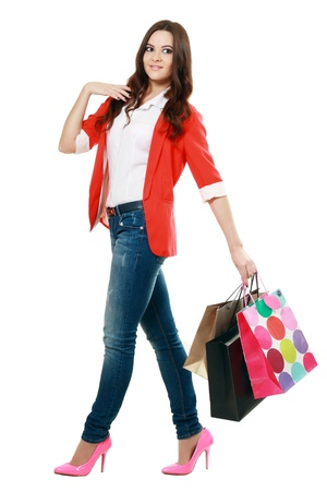 Shopping woman walking and holding bags - isolated over white photo