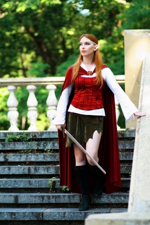 Elf warrior girl on the rock in red cloak posing outdoor photo
