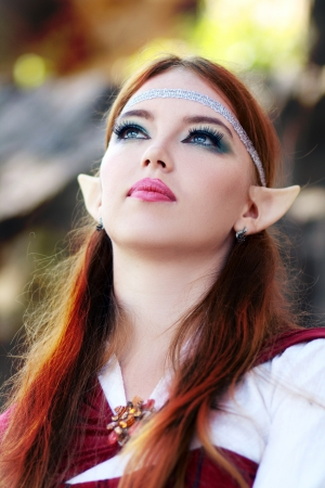 Elf warrior girl on the rock in red cloak posing outdoor close up face photo