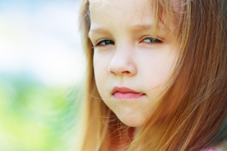 Closeup portrait of little girl outside with a questioning expression photo