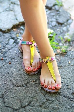 sandalia: Pies de la chica joven que llevaba sandalias de verano y de pie en la antigua carretera de asfalto.