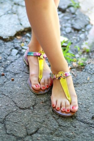 Young girl's feet wearing summer sandals and standing on old asphalt road.