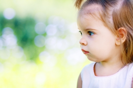 expresses: Adorable little girl serene and still. Her face expresses a thoughtful and contemplative look as she enjoys the outdoors. 1