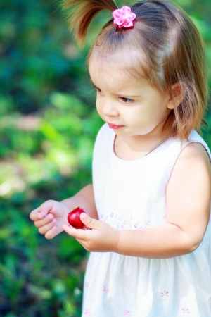 A little girl eating plum outdoor in sunny summer day photo