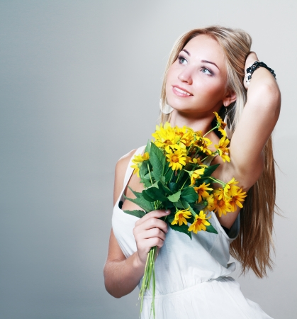 beautiful blond woman holding yellow flowers photo
