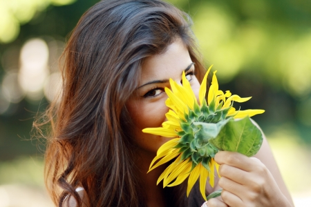 Cute young sensual woman smelling sunflower  photo