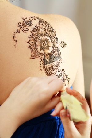 The process of drawing henna applying on the back of a young girl of Arabic inscriptions, with a focus on the tattoo
