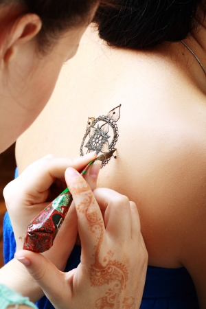 The process of drawing henna applying on the back of a young girl of Arabic inscriptions, with a focus on the tattoo  photo