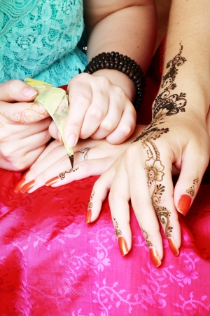 Image detail of henna being applied to hand  photo