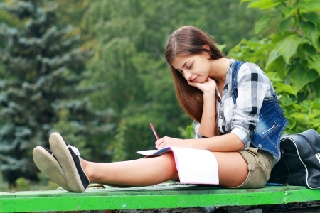 Beautiful school or college girl sitting on the bench with book and bag studing in a park  photo